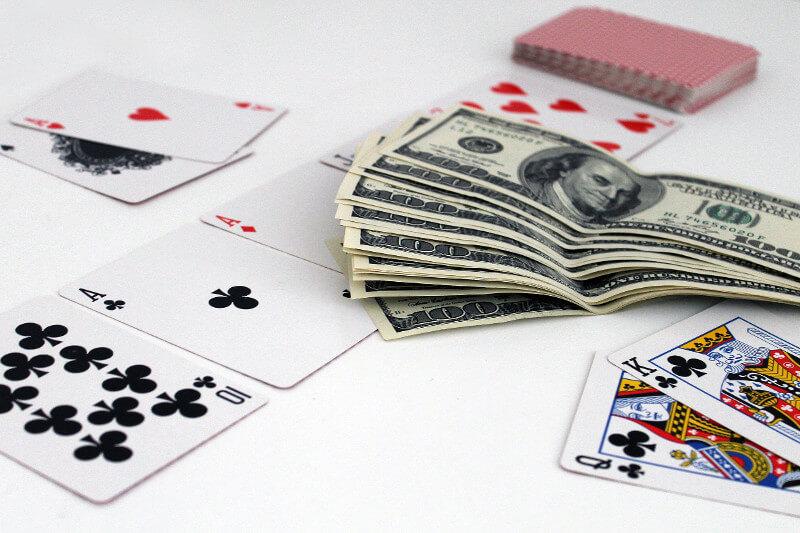 kartu poker dan uang di atas meja